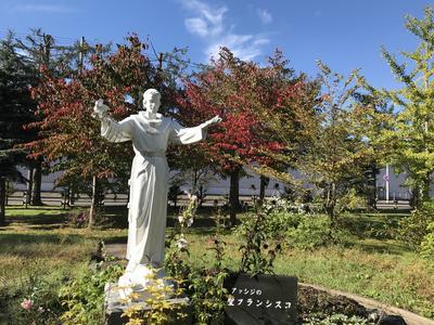 桜の紅葉を背景にした聖フランシスコ像